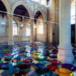 Usando espelhos circulares coloridos, artista transforma igreja centenária em fantástica instalação artística